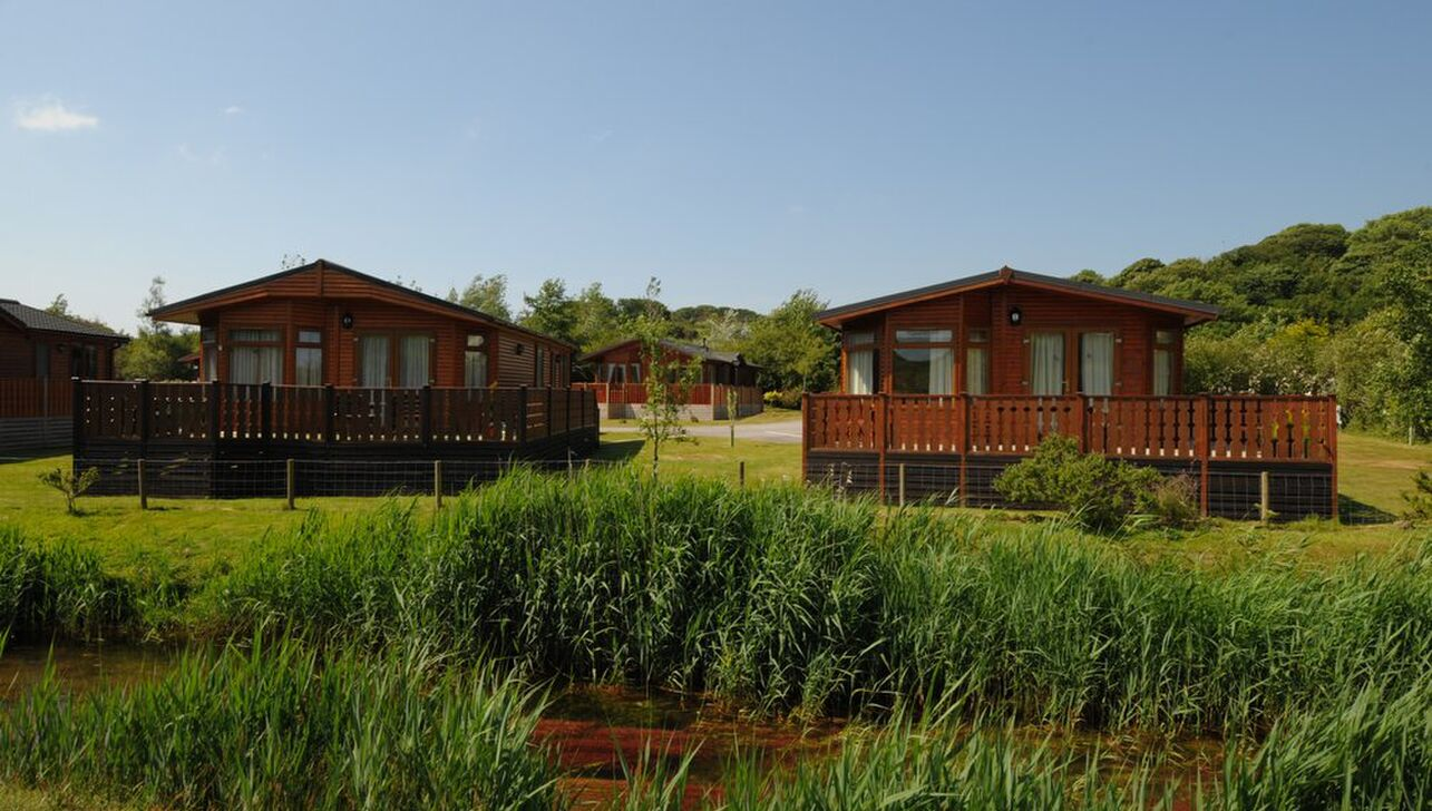Log cabins by the river at  River Valley Country Park in Cornwall
